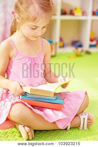 Cute little schoolgirl sitting at home on the floor with books and preparing to go to first class, doing homework, back to school