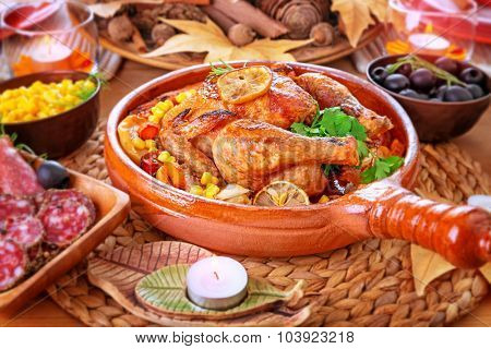 Traditional Thanksgiving day dinner, tasty roasted turkey, cold cuts, corn and olives on the festive table decorated with dry maple leaves and candles