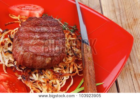 grilled beef fillet pieces on noodles , red hot chili pepper with tomato on red plate over wood table