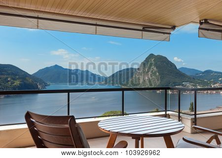 beautiful terrace with table and chairs overlooking the lake