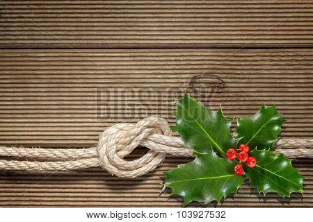 Christmas holly with with red berries on wood texture