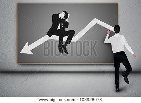 Young business man write down arrow on blackboard