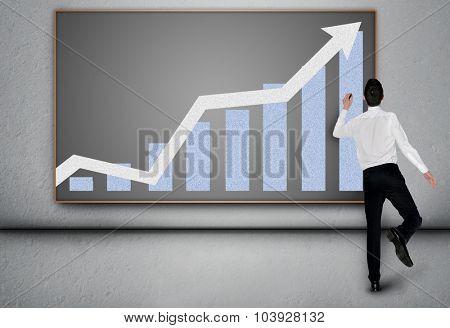 Young business man write success arrow on blackboard