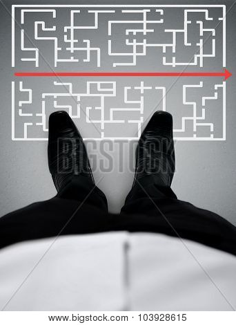 Maze solution and business man shoes close-up