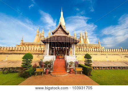 Golden Buddhist Pagoda Of Phra That Luang Temple Under Blue Sky. Vientiane, Laos Travel Landscape An