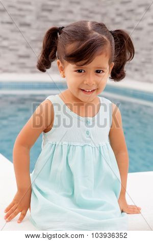 Funny little girl with pigtails sitting near the pool