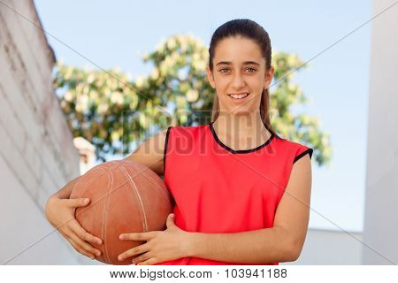Teenager student girl with a basket ball outdoor