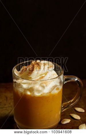 Pumpkin spice latte on moody background, selective focus