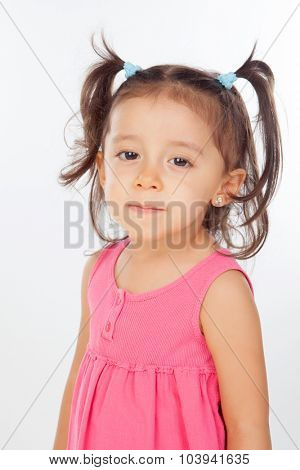 Funny little girl with pigtails and pink dress isolated on a white background