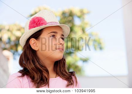 Pensive child girl ten year old with a hat on the street