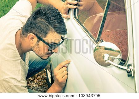 Young Handsome Man With Sunglasses Inspecting A Vintage Car Body At Second Hand Trade