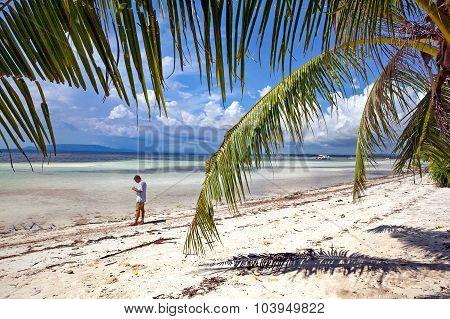 Man Beachcombing Tropical Island