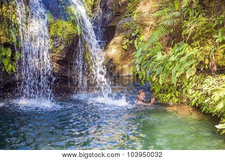Asian Woman Enjoys Tropical Waterfall