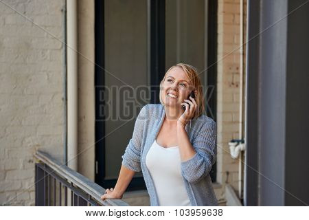 young business casual woman talking on mobile cell phone outdoors