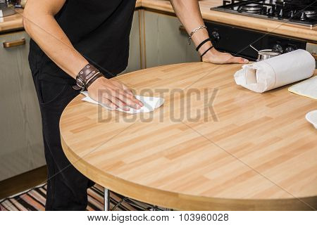 Young Man Wiping Table with Paper Towel in Kitchen