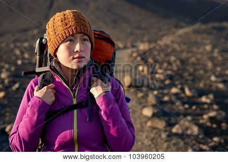 portrait of young asian woman hiking in Iceland with backpack and outdoor gear on vacation holiday travel adventure