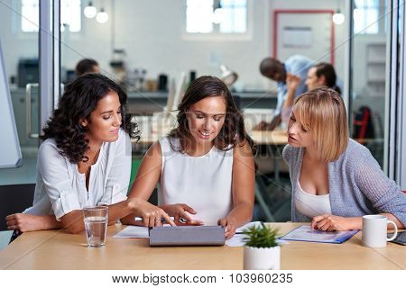 diverse multiracial colleagues discussing tech startup business ideas on tablet computer device
