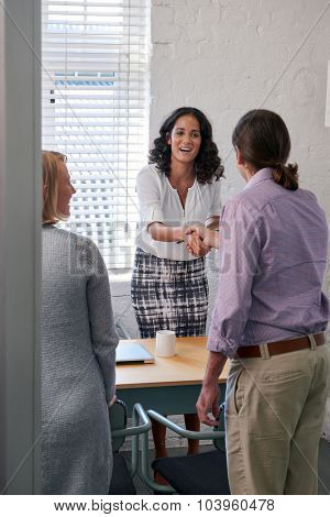 happy business financial advisor woman shaking hands with couple clients to discuss financial services