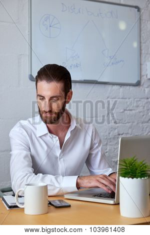 professional young business man working on laptop computer at office desk