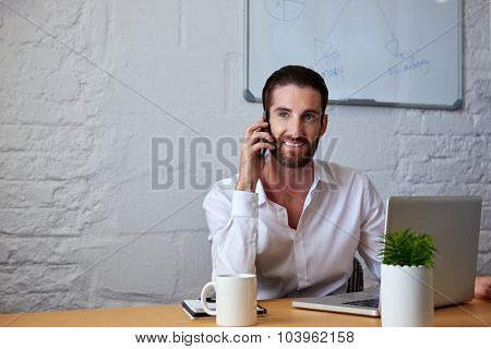 professional business man talking on mobile cell phone to clients in office with laptop computer