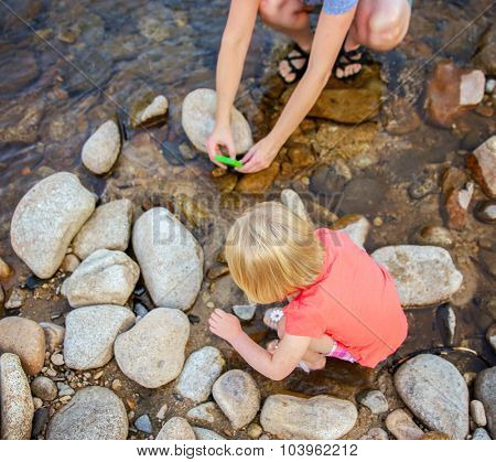 a mother taking a photo with a cell phone of her child looking at a frog in a stream or river during summer