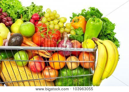 Grocery shopping cart with vegetables and fruits. Isolated on white.