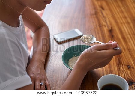 young woman having breakfast cereal and coffee