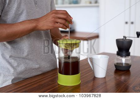 Young man preparing coffee for breakfast