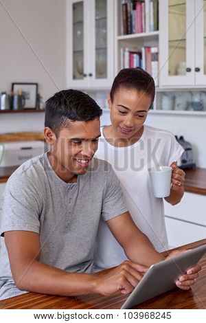 mixed race couple relaxing with coffee tablet computer in home kitchen