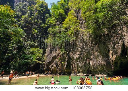 KO LANTA, THAILAND, FEBRUARY 09, 2015 : Some tourists are bathing in the natural sea pool of the Emerald cave near the Ko Lanta island in Thailand