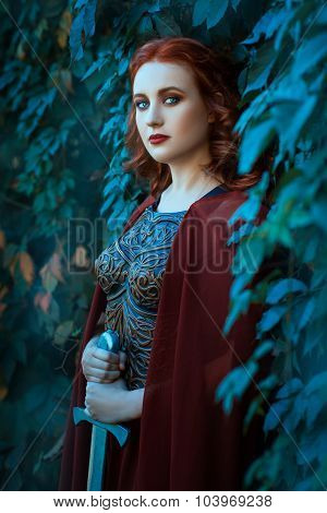 Girl With A Sword Standing In The Bushes Of Grapes.