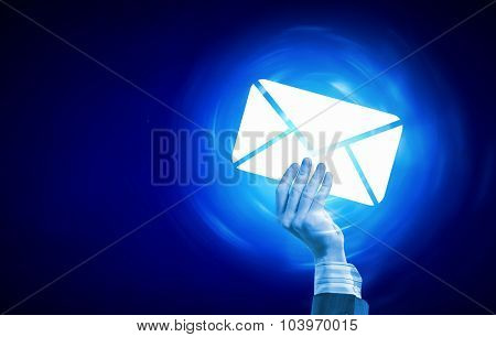 Person hand holding glowing email symbol on blue background