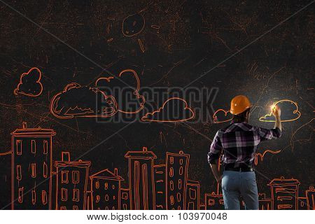 Back view of man engineer drawing building sketches on wall