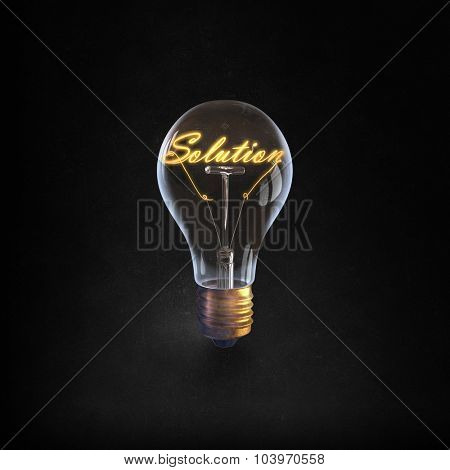Glowing glass light bulb with word solution inside