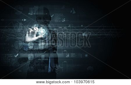 Young businessman pressing high tech circle icon on media screen