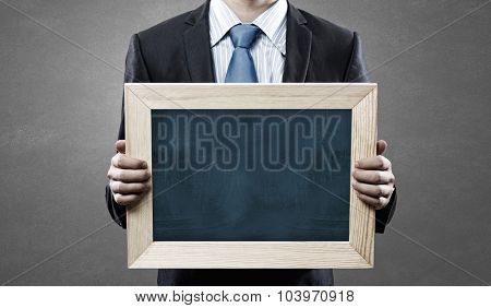 Unrecognizable businessman holding blank chalkboard. Place your text