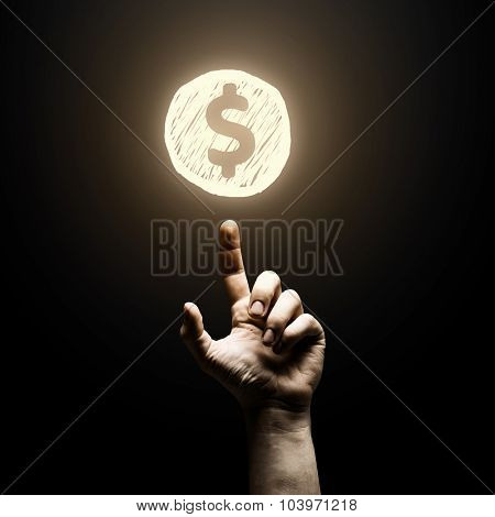 Human finger pointing at dollar sign on black background