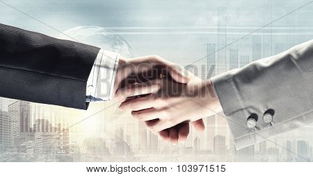 Close up of business handshake on digital background