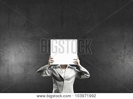 Businesswoman hiding her face behind blank paper list