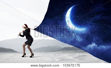 Santa woman pulling clothing with moon on rope