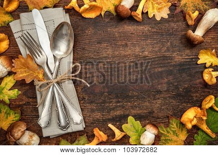 Thanksgiving autumn place setting with cutlery and arrangement of colorful fall leaves and mushrooms