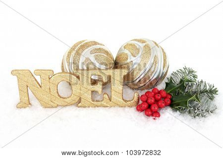 Noel gold glitter sign with christmas holly, fir and bauble decorations on snow over white background.