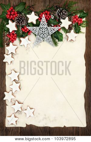 Christmas background border with gingerbread cookies, silver star and ball decorations, holly, ivy, fir and pine cones on parchment paper over old oak wood.