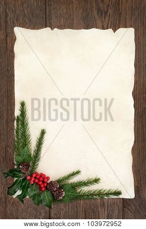 Christmas background border with holly, ivy and fir on parchment paper over old oak wood.