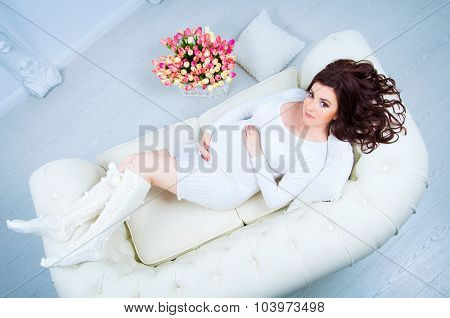 Pregnant Woman Lying On A Sofa Near A Basket With Tulips