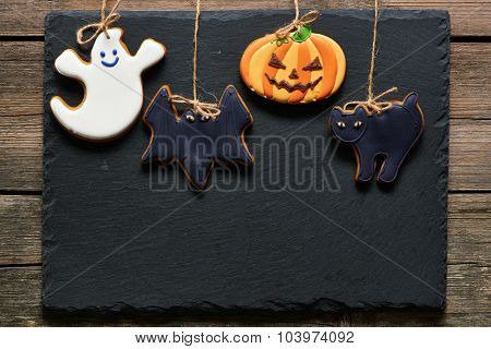 Halloween homemade gingerbread cookies over slate background