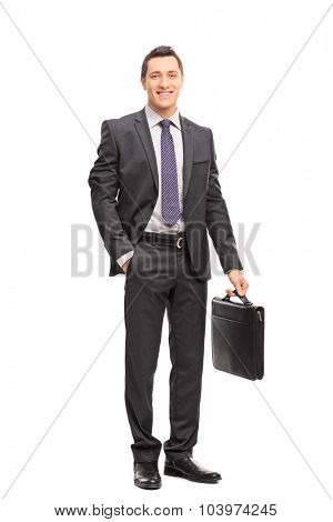 Full length portrait of a young businessman in a gray suit holding a briefcase and looking at the camera isolated on white background
