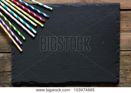 Drinking straws on slate background