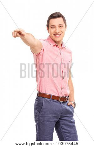 Vertical shot of a confident young man pointing forward with his hand and looking at the camera isolated on white background