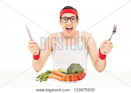 Nerdy athlete eating vegetables with knife and fork seated at a white table isolated on white background